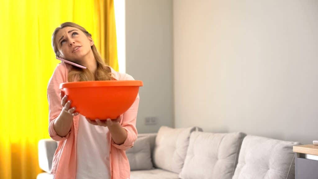 Holding a bowl to catch water leaking from ceiling